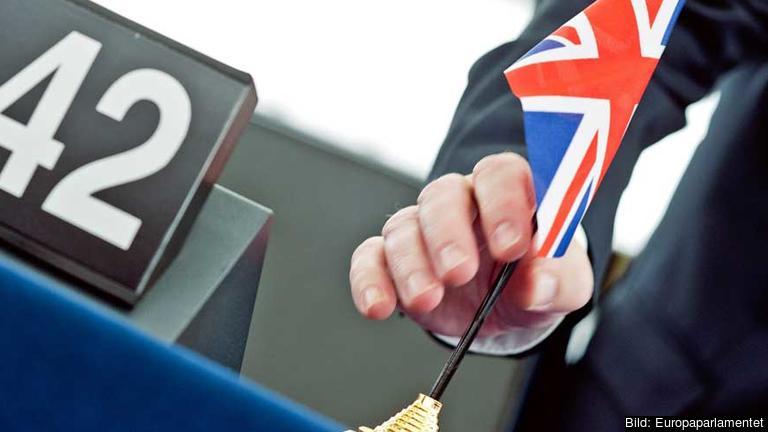 En ledamot i Europaparlamentet ställer fram den brittiska flaggan i plenum.